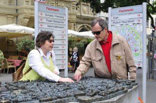 Visitante cego tateia réplica do centro antigo de Erfurt com auxílio de guia no Mercado de Peixes - Foto: Divulgação DZT