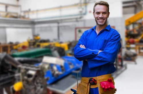 Digital composition of mechanic standing with arms crossed in factory