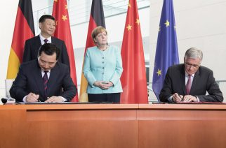 Lu Chun, Presidente da China Three Gorges Corporation, e Hubert Lienhard, Presidente e CEO do Grupo Voith, assinam parceria em Berlim. Ao fundo, os presidentes da China e Alemanha, Xi Jinping e Angela Merkel, respectivamente.