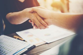 Close-up of two business people shaking hands while sitting at the working place.